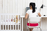 Woman working at home office while her baby lying in children's bed - DRF000937