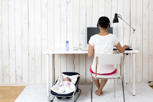 Woman working at home office while her baby lying in bouncy seat - DRF000944