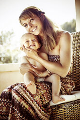 Happy mother holding her baby - GDF000349