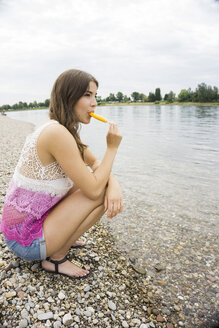 Portrait of young woman with ice lolly on the beach - UUF001198