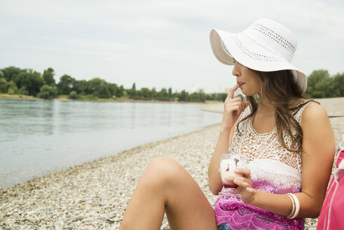 Young woman wearing summer hat relaxing on the beach - UUF001201