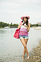 Young woman with hat and bag standing at waterside of Rhine river - UUF001204