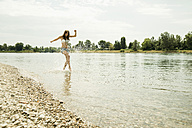Young woman running at waterside of Rhine river - UUF001210