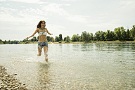 Young woman running at waterside of Rhine river - UUF001212