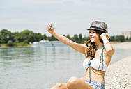 Portrait of young woman taking a selfie with her smartphone on the beach - UUF001229