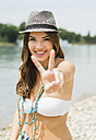 Portrait of smiling young woman showing victory sign on the beach - UUF001230