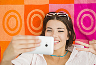 Portrait of smiling young woman lying on beach towel taking a selfie, elevated view - UUF001292