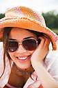 Portrait of smiling young woman wearing summer hat and sun glasses - UUF001273