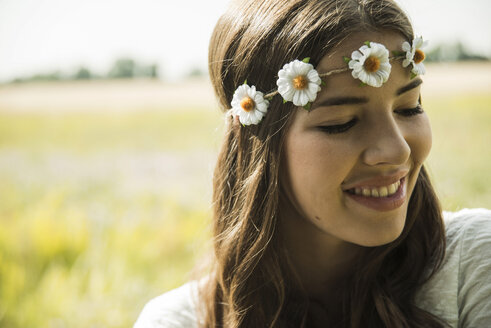 Portrait of smiling young woman wearing floral wreath - UUF001235