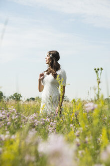 Young smiling woman standing on flower meadow - UUF001241