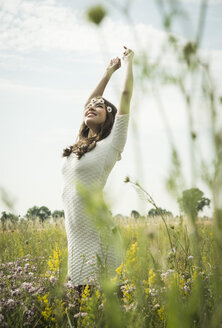 Happy young woman standing on flower meadow - UUF001246
