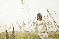 Young woman standing on flower meadow looking into the sky - UUF001258
