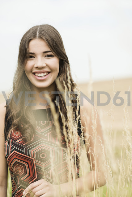 Portrait of a happy young woman standing on an autumnal  meadow - UUF001301