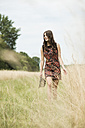 Young woman walking on a meadow - UUF001312