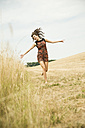 Young woman running on a harvested meadow - UUF001324