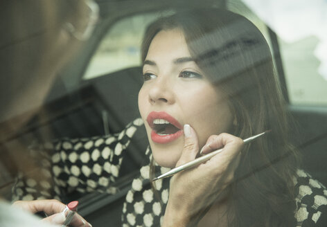 Female visagiste applying lipstick on young woman's lips - UUF001327
