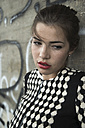 Portrait of sad young woman with red lips in front of wall with graffiti - UUF001336