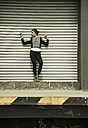 Young woman posing in front of roller shutter - UUF001341