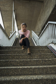 Young woman sitting on staircase waiting - UUF001364