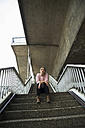 Young woman sitting on staircase waiting - UUF001348