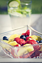 Glass bowl of fruit salad and glass of lime lemonade in the background - SARF000717