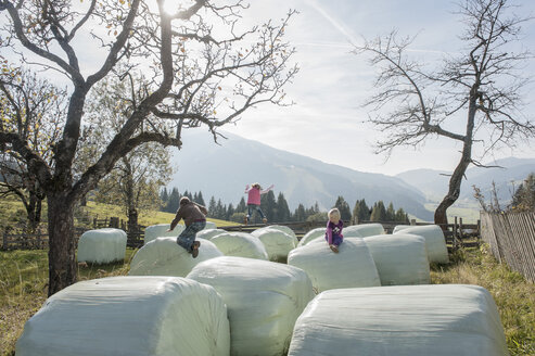 Three children playing on bales of straw - HHF004834