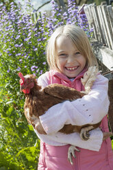 Happy girl hugging hen - HHF004841