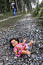 Austria, Linz, stripped doll lying on forest track while man going away - EJW000446