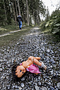 Austria, Linz, stripped doll lying on forest track while man going away - EJW000447
