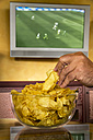 Man's hand taking potato chips from a glass bowl in front of flatscreen TV broadcasting a soccer match - EJWF000448
