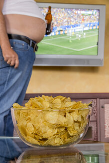 Man with naked beer belly holding beer bottle in front of flatscreen TV broadcasting a soccer match, partial view - EJWF000449