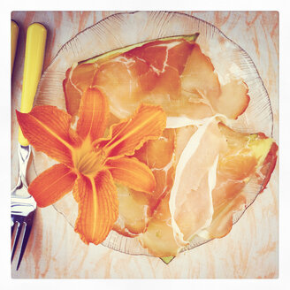 Ham and edible flower on plate - GWF002916