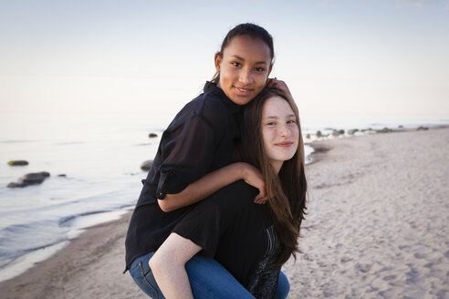 Germany, Ruegen, Two young female friends at the beach, Piggyback - OJF000046