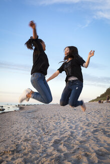 Germany, Ruegen, Two young female friends jumping at the beach - OJF000050
