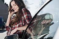 Young woman at car on cell phone - FEXF000099