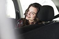 Smiling young woman on back seat of a car - FEXF000104