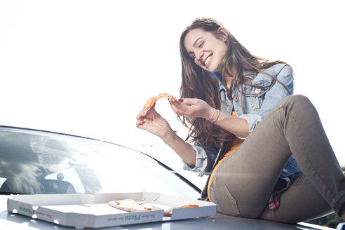 Happy young woman eating pizza on car hood - FEXF000122