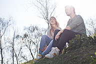 Relaxed young couple sitting on meadow - FEXF000126
