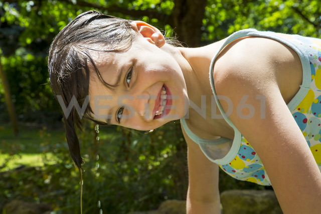 Portrait of laughing little girl with dripping wet hair in the garden - LVF001585