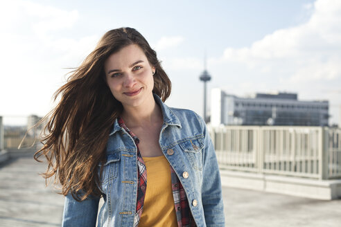 Germany, North Rhine-Westphalia, Cologne, portrait of smiling young woman standing on parking level - FEXF000133