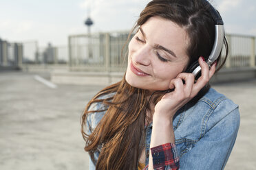 Germany, North Rhine-Westphalia, Cologne, portrait of smiling young woman listening music with headphones - FEXF000138