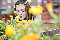 Portrait of smiling young woman enjoying flowers - FEXF000143