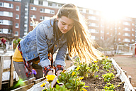 Portrait of young woman at raised bed in front of multi-family house - FEXF000145