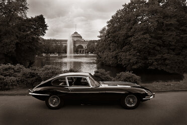 Germany, Hesse, Wiesbaden, Jaguar E-Type S1 Coupe driving in front of spa park - BSC000436