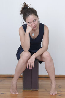 Frustrated woman sitting on suitcase - MW000060