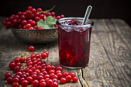 Jam jar of currant jelly, bowl and red currants, Ribes rubrum, on wooden table - LVF001603