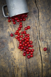 Metal jar of red currants, Ribes rubrum, on dark wooden table, elevated view - LVF001634
