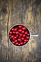 Metal jar of red currants, Ribes rubrum, on dark wooden table, elevated view - LVF001607