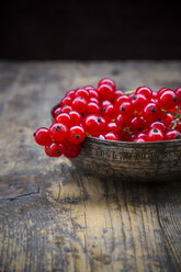 Bowl of red currants, Ribes rubrum, on dark wooden table, partial view - LVF001610