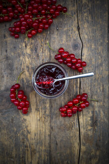 Jam jar of currant jelly and red currants, Ribes rubrum, on wooden table, elevated view - LVF001612